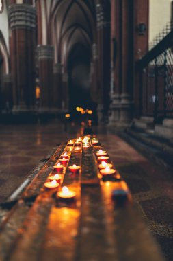 Rows of burning spiritual candles in a church