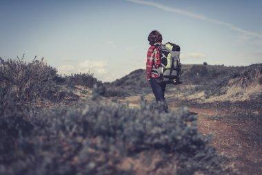 Backpacker walking through hilly scrub