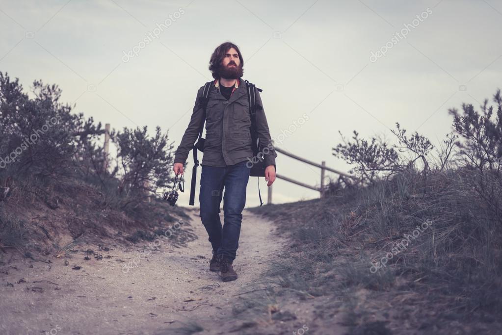 Backpacker walking down a sandy trail