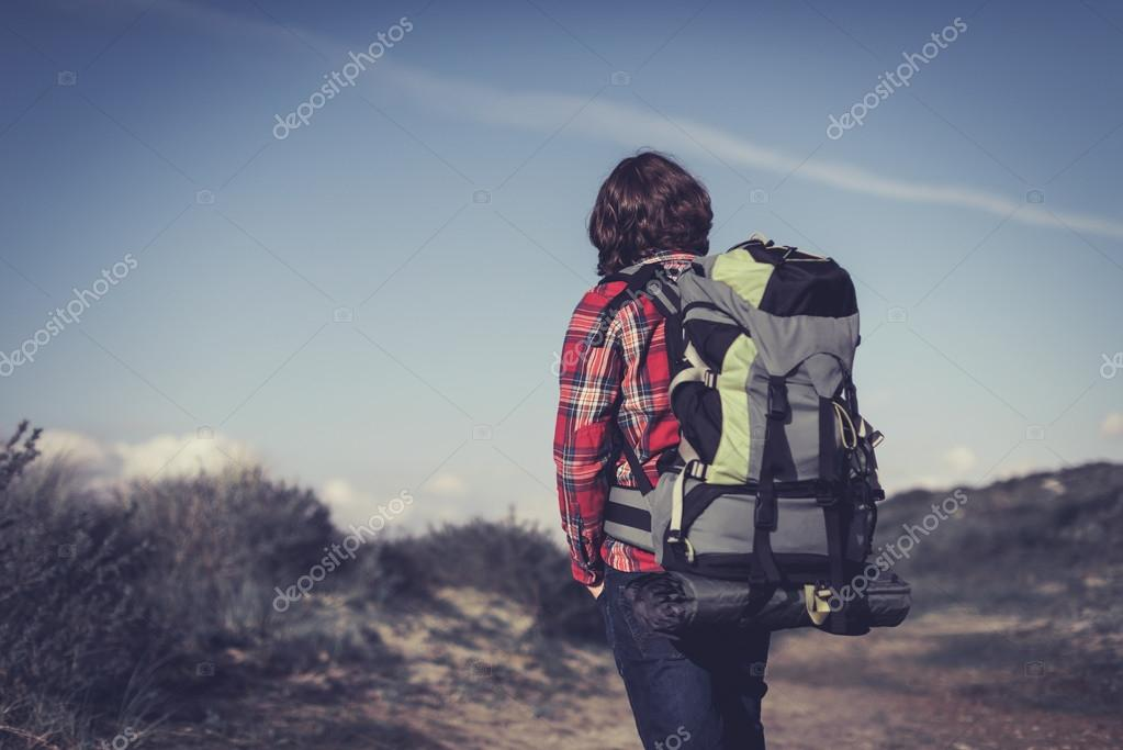 Backpacker walking through hilly scrub