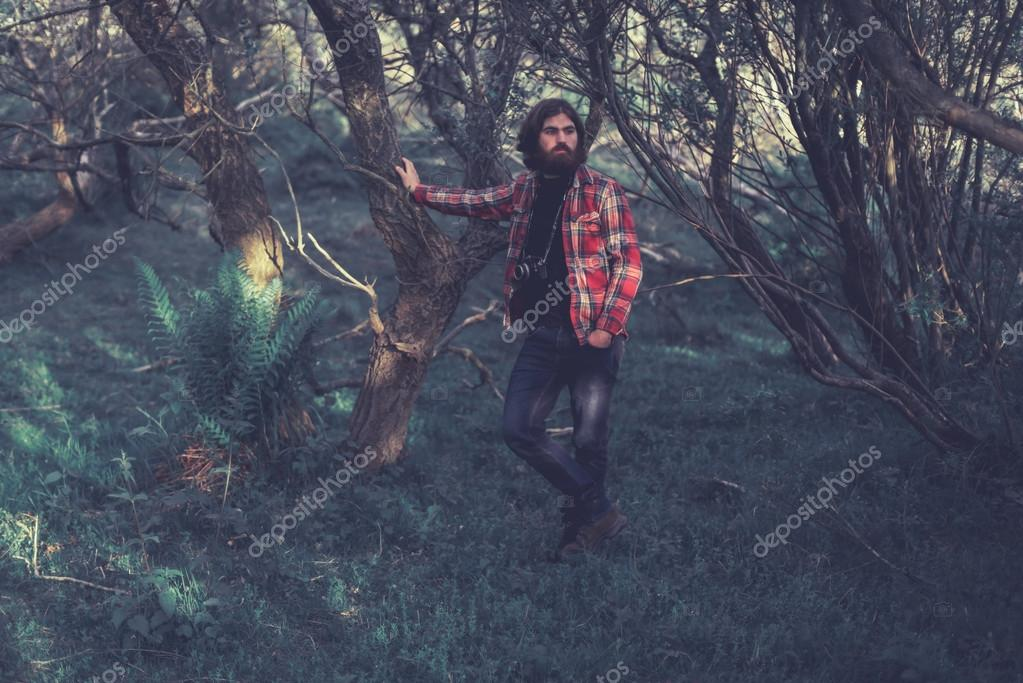 Man in Leaning Against Tree in Forest