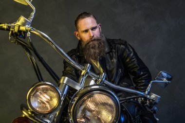 Thoughtful Bearded Man Sitting on his Motorcycle