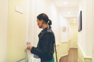 Brunette woman unlocking door