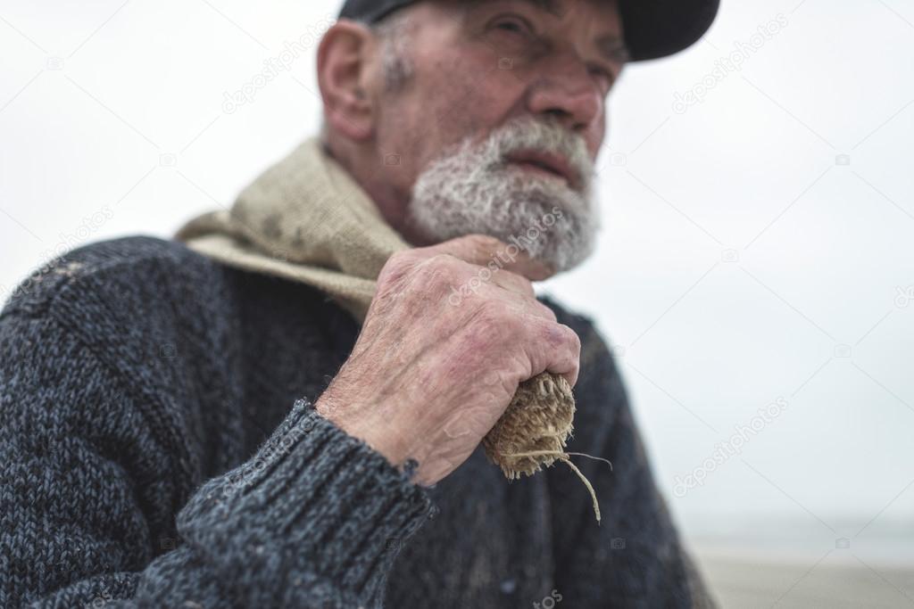 Hand of beachcomber holding burlap sack