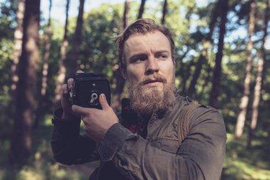 Alert beard man holding vintage camera in forest. stock vector
