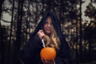 woman with pumpkin in forest
