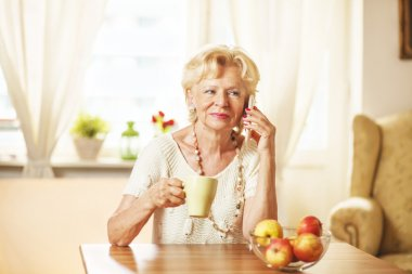 Blonde eldery woman using cell phone, at home