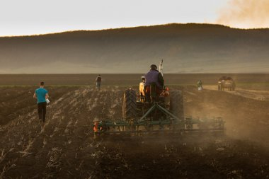 Family working the field with hand and tractor. People doing cla