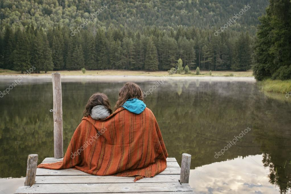 Mother and daughter sitting on a jetty with lake and forest in f
