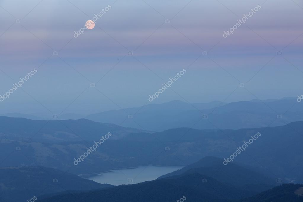 Full moon over mountains and lake
