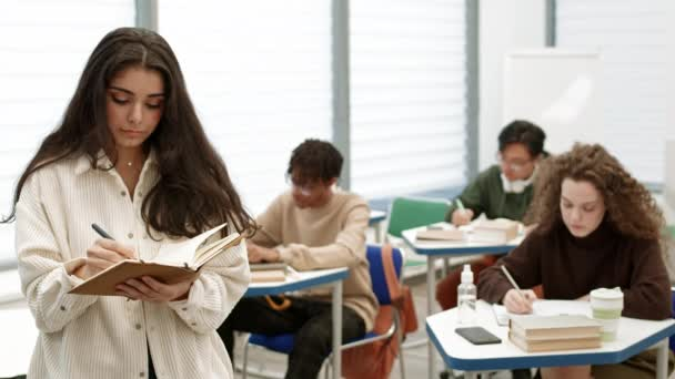 Medium POV mladé ženy smíšené rasy, která si dělá poznámky do sešitu, pak je zavírá, dívá se nahoru a usmívá se před kamerou, stojí před rozmazanými studenty sedícími u psacích stolů, píše ve třídě