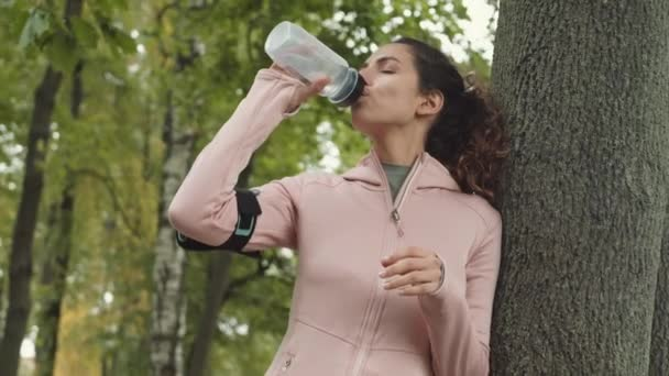 Pan shot of young Caucasian sportswoman wearing sport clothes standing leaning on tree in forest and drinking water from sport bottle