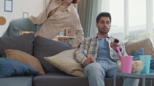 Mittellanger junger Mixed-Race-Mann auf Couch sitzend, Fernsehsender schaltend mit entfernter, rothaariger kaukasischer Freundin, die über Sofa-Rücken springt, sich Freund anschließt, Paar spricht