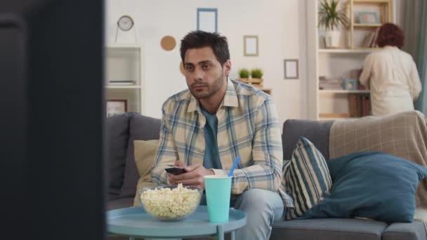 Mittlere Langzeitaufnahme eines dunkelhaarigen Mixed-Race-jungen Mannes, der zu Hause auf der Couch im Wohnzimmer sitzt, den Fernseher in der Hand hält, Programm anschaut, verschwommenes Mädchen, das Buch aus dem Regal nimmt