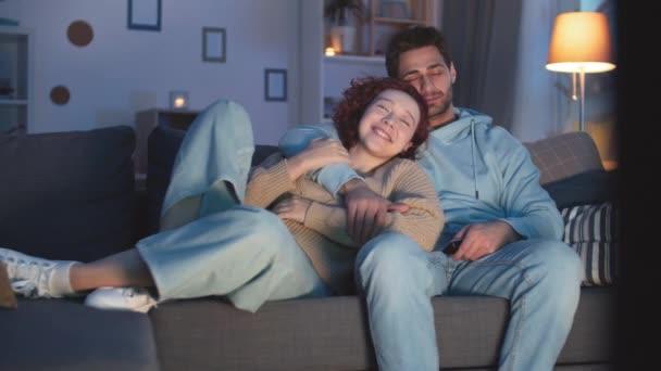 Steadicam záběr šťastného páru, jak se v noci dívá na televizi, usmívá se, mazlí. Červenovlasá běloška opírající se o hruď milujícího přítele ze smíšeného závodu na gauči doma