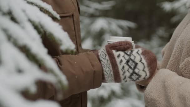 Detailní záběr nerozpoznatelného muže v rukavicích zahřívající ruce nerozpoznatelné ženy stojící poblíž v zimním lese a držící šálek kávy