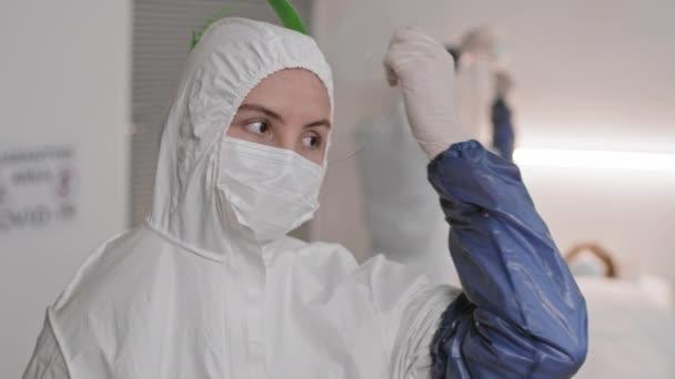 Barna szemű fehér orvos közelkép POV-ja fehér védőruhát visel, leveszi az arcvédőt és letörli az izzadságot a homlokáról hosszú nap után, majd a kamerába néz a homályos kórházi szobában.