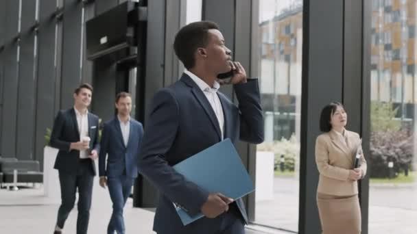 Közepes felvétel fiatal, jóképű afrikai üzletemberről, elegáns kék öltönyben az irodateremben, telefonbeszélgetéssel a kollégájával.