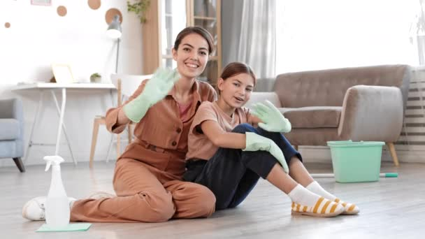 Wide shot of young mixed-race woman and her teenage daughter both wearing rubber gloves sitting on floor in living boom, looking at camera and waving hands before cleaning their house