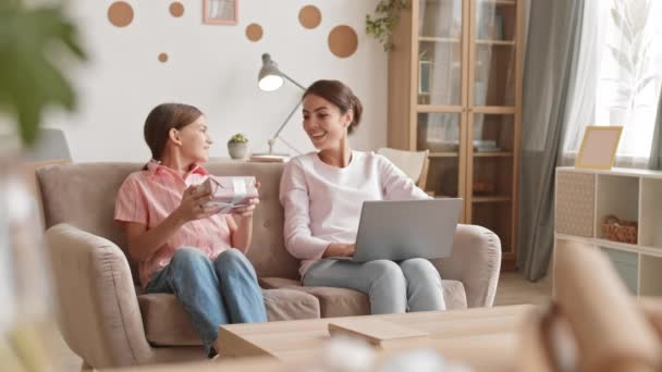 Lockdown of beautiful mixed-race woman sitting on couch in living room and working on laptop while her teenage daughter coming and giving her a birthday present