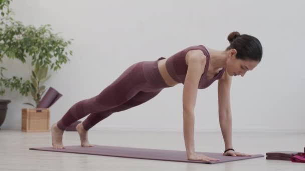 Široký záběr sportovní mladé bělošky na sobě sportovní oblečení dělá jóga cvičení na podložce jógy uvnitř