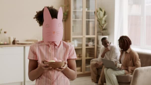 Közepes lövés felismerhetetlen gyermek visel kézzel készített rózsaszín húsvéti nyuszi maszk áll a nappaliban, gazdaság tál színes tojások a kezében, elmosódott szülők ül a kanapén a háttérben