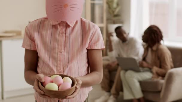 Közepes lövés vágott felismerhetetlen személy visel kézzel készített rózsaszín húsvéti nyuszi maszk áll a nappaliban, gazdaság tál színes tojások a kezében, elmosódott emberek ülnek a kanapén a háttérben
