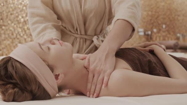 Uzamčení nerozpoznatelné masérky pro mladou bělošku ležící na masážním stole v lázeňském salonu
