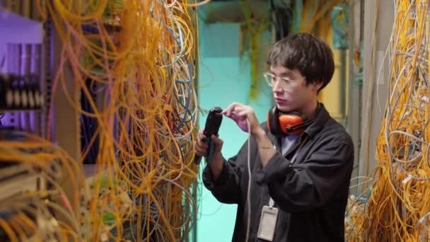 Mittlere Aufnahme eines jungen asiatischen IT-Technikers mit Streetwear, Brille und Kopfhörer am Hals, der im Serverraum steht und Drähte verbindet