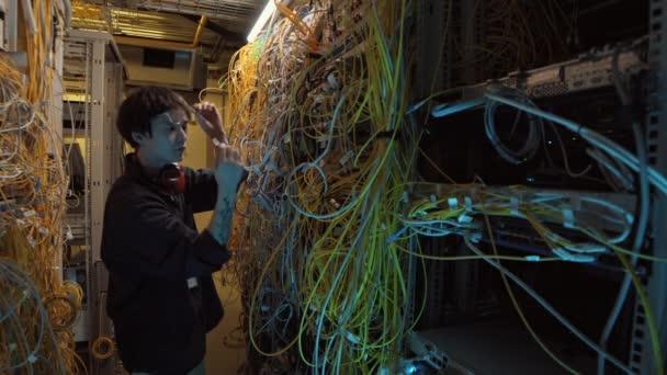 Střední záběr mladého asijského IT inženýra v neformálním oblečení konfigurující serverová zařízení při stání v moderním datovém centru