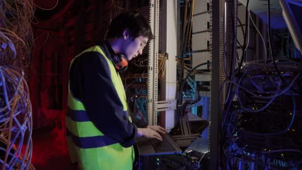 Střední záběr mladého asijského IT inženýra ve speciální uniformě a brýlích stojící v datovém centru a hovořící s kolegou mobilním telefonem