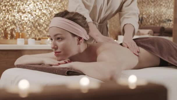Lockdown junge attraktive kaukasische Frau liegt auf Massagetisch im Wellness-Center und genießt erholsame Rückenmassage