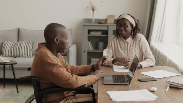 Lezárása fiatal afrikai fogyatékos férfi ül tolószéken laptop a nappaliban, kártyával a kezében, és hogy az online vásárlás segítségével a barátnője ül a közelben