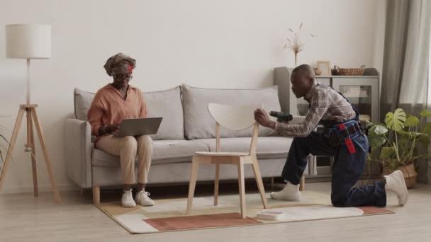 Weite Aufnahme von afrikanischen Handwerker in Uniform Montage Holzstuhl mit Schraubenzieher, während afroamerikanische Frau mit Laptop. Dann zufriedene Frau auf Stuhl