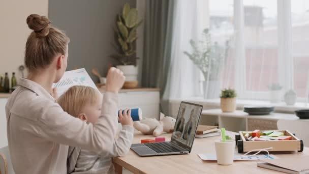 Pohled z boku na mladou bělošku pracující doma u psacího stolu, ukazující dokumenty a mající online konferenci přes notebook, batole sedící na klíně, pijící z kojenecké láhve