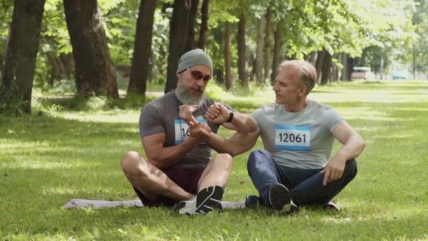 Weitschussbild eines älteren männlichen Trainers, der auf einer Gummimatte auf dem Rasen im Wald sitzt und den Puls eines Sportlers mittleren Alters misst, der beim Gespräch nach dem Training in der Nähe sitzt