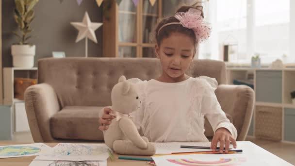Dereka kis imádnivaló vegyes bőrű lány ül asztalnál a nappaliban, kezében játékmaci, rajz és beszéd