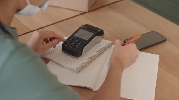 Zadní pohled na nerozpoznatelnou smíšenou servírku v uniformě a lékařské masce, která sedí u dřevěného stolu, mačká tlačítka zařízení pro bezkontaktní platby a dělá si poznámky do sešitu
