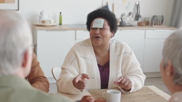 Hüftschwung über der Schulter fröhlicher älterer Menschen, die am Tisch sitzen, Post-it-Notizspiel spielen, kaukasischer Mann, der Fragen zu seinem Charakter stellt, antwortet, afrikanische Frau lächelt, applaudiert