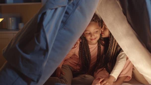 Středně dlouhá pětiletá africká dívka šeptá do ucha své starší sestře tajemství, děti se usmívají, sedí v polštářové pevnosti ve světle lampy v noci