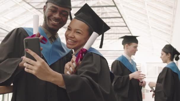 Střední záběr mladé smíšené rasy žena a africký muž na sobě vysokoškolské šaty a klobouky stojící spolu uvnitř, držící diplomy a dělat selfie pomocí mobilní kamery
