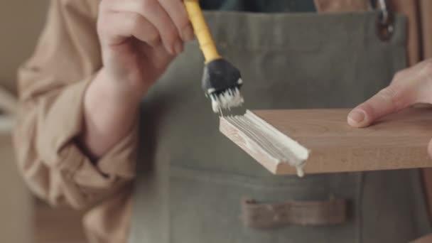 Detailní záběr rukou nerozpoznatelné ženské truhlářské nanášení lepidla na dřevěnou desku pomocí speciálního kartáče