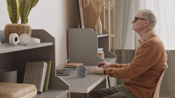 Mittlere Langsamkeit eines blinden älteren Mannes mit schwarzer Brille, der zu Hause am Schreibtisch sitzt und nach einer Tasse Tee tastet