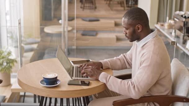 Střední side-view záběr moderního afroamerického muže v elegantním casualwear pracující na notebooku u jídelního stolu