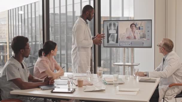 Střední zpomalení týmu profesionálních multietnických radiologů na videokonferenci s kolegyní na monitoru, vyšetření rentgenu hrudníku pacienta a přemýšlení o diagnóze