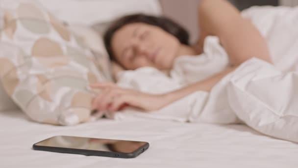 Eingeschlossenes Smartphone im Bett liegend, verschwommene Frau im Hintergrund tastet Gerät mit der Hand ab, schaltet Wecker aus