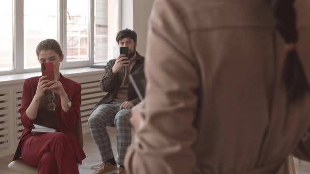 Mittellanges multiethnisches Publikum, das auf Stühlen im Konferenzraum sitzt, Videoaufnahmen mit unkenntlichen Darstellern auf Smartphones und Tablet-Computern