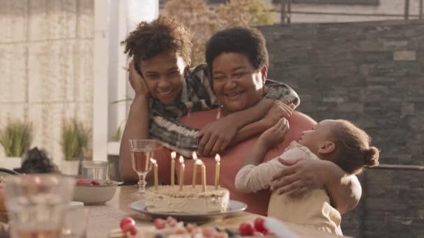 Středně vyspělá africká žena sedící venku u stolu, její dospívající muž a pětiletá vnučka ji objímají a pak všichni sfouknou svíčky na narozeninový dort