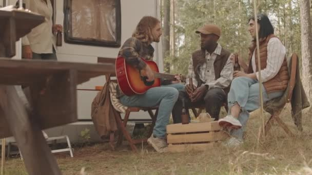 Slowmo shot of man playing guitar to friends, sitting together with bottles of beer in summer forest near tiny home on wheels