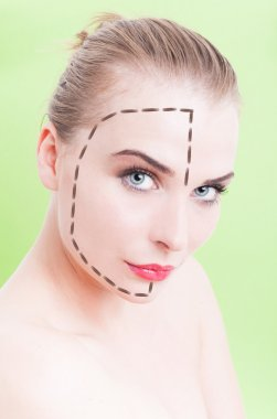 Beautiful young female face with facelift marks over green backg